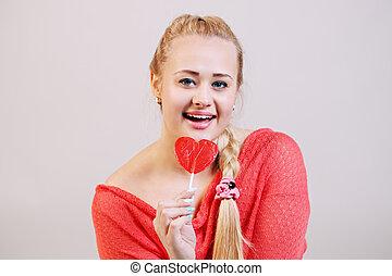 blonde holding a lollipop