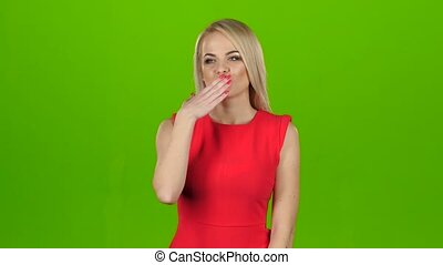 Blonde in a red dress gives out kisses, girl model smiling and making kisses with her both hands, different emotions on face, green screen background in isolated studio, close up