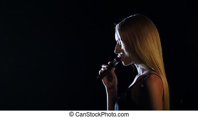 Blonde in a spacious room smokes an electronic cigarette....