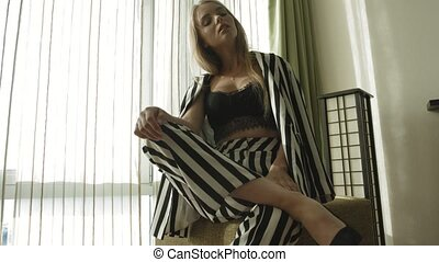 Blonde in a striped suit and black bra sits on a soft ottoman near the window