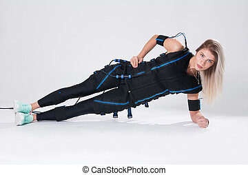 Blonde in an electric muscular suit for stimulation makes an exercise on the rug.