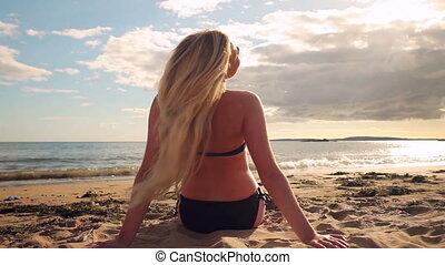 Blonde in bikini sitting on the beach