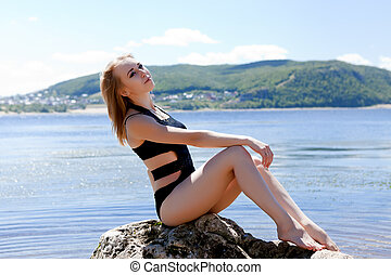 blonde in black bathing suit sitting on large rock