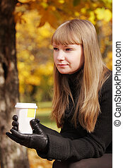 Blonde in black coat with cup