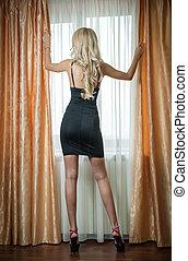 Blonde in black dress in window