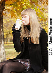 Blonde in black drinking from cup