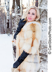 Blonde in fur coat, leather gloves poses near bir?h outdoor at winter day in forest