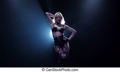 Blonde in leather costume dances in black studio. Slow motion