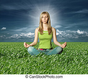 Blonde in lotus pose in green grass