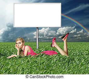 Blonde in pink dress in green grass