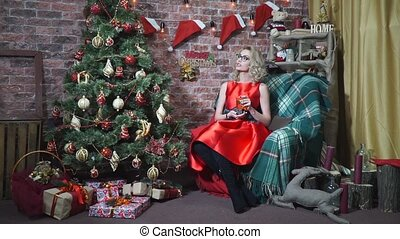 Blonde in red dress sitting in a chair with a cup of tea at the Christmas tree