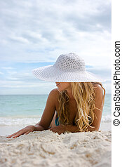 Blonde in white hat on the beach