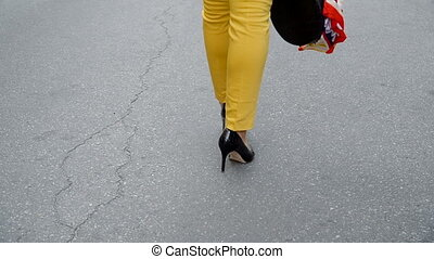 Blonde in yellow trousers and a black hat posing in the...