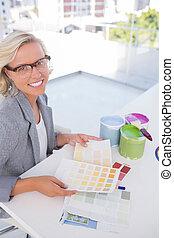Blonde interior designer holding colour charts