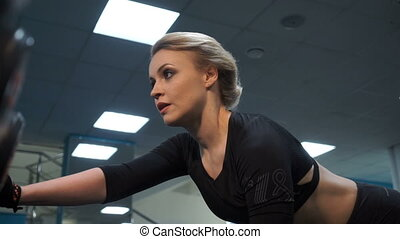Blonde is doing sports close-up - Athlete trains in the gym