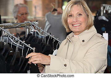 blonde lady doing shopping in a clothes shop