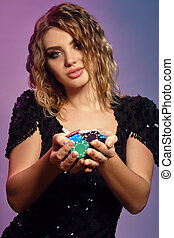 Blonde lady in black sequin dress is holding handful of multicolored chips, posing on colorful studio background. Gambling, poker, casino. Close-up.