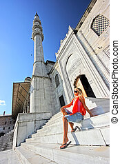 Blonde lady sitting in front of the mosque