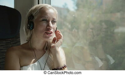 Blonde listening music in headphones in the train