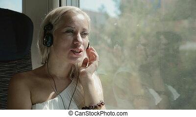 Blonde listening music in headphones in the train