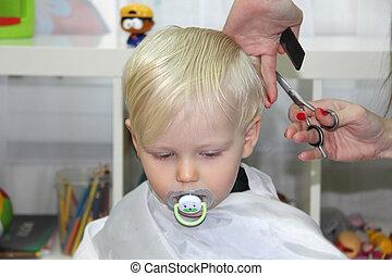 Blonde Little boy cut their hair in a childrens hairdresser