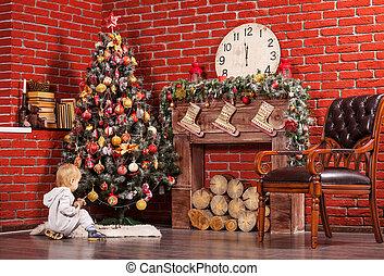 Blonde little boy playing near Christmas tree