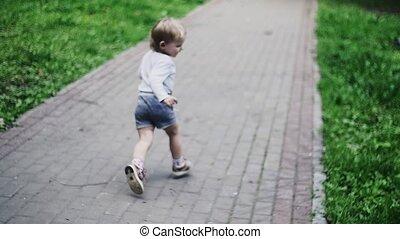 Blonde little boy running on playground in summer park. Childhood. Happiness