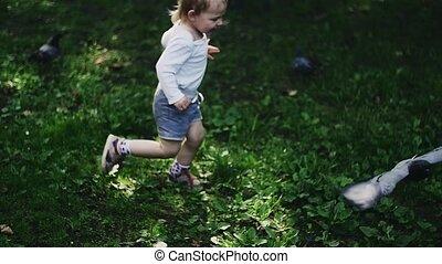 Blonde little boy running on playground in summer park for dove. Childhood.