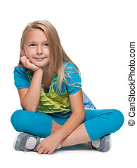 Blonde little girl sits on the floor