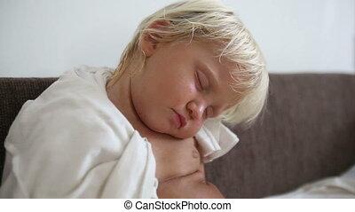 blonde little girl sleeps on sofa closeup