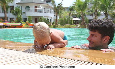 blonde little girl tries to scramble out of swimming pool by...