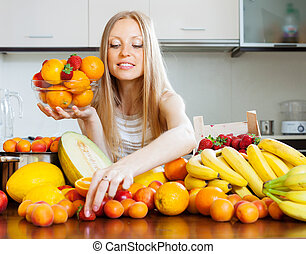 blonde long-haired woman choosing fruits