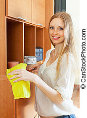 Blonde long-haired woman cleaning furniture
