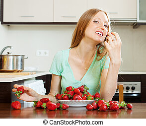 woman eating strawberry in home kitchen