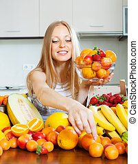 blonde long-haired woman taking fruits