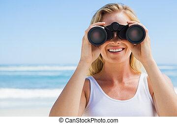 Blonde looking through binoculars on the beach