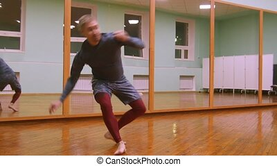Blonde male fighter performs martial tricks with dance...