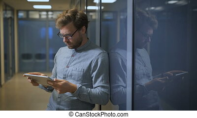 Blonde man in a business center monitors the news on social networks