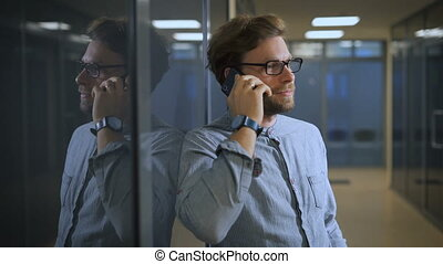 Blonde man in a business center talking on his black smartphone.