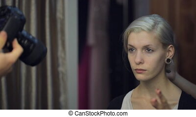 Blonde model sits in dressing room and looks at photographer.