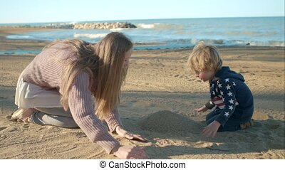 Mom and son playing with sand on the beach.