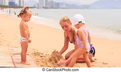 blonde mother and two little girls build sand castle on beach