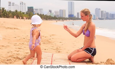 blonde mother and two little girls play on sand beach