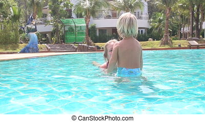 blonde mother plays with daughter in pool