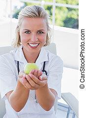 Blonde nurse holding a green apple