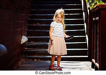 Blonde on a wooden staircase enjoying summer vacation