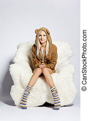 portrait of beautiful blonde girl in brown plush hud with bear ears sitting on big white furry arm-chair