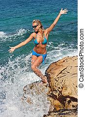 Blonde on rocky beach