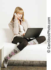 Blonde on sofa with laptop and cellphone