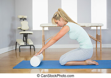 Blonde patient sitting on floor doing exercise